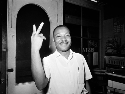 Martin Luther King Jr giving peace sign at St Augustince boycott in 1964 photograph