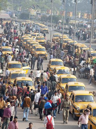 Yellow Kolkata Taxis and Commuters at Howrah Railway Station, Howrah, Kolkata (Calcutta), India Photographic Print by Annie Owen