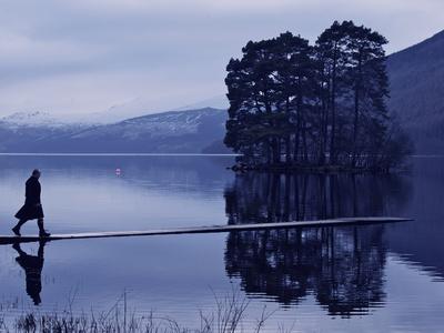 A Man in a Kilt Walks on a Shallow Pier on a Lake Fotoprint av Jim Richardson