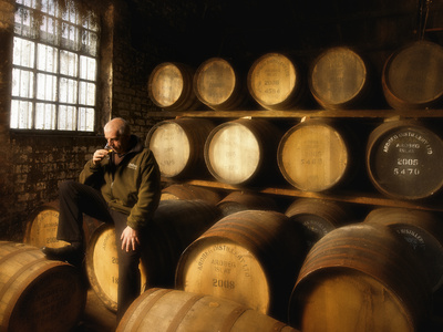 A Worker Tastes Whisky in a Distillery Surrounded by Aging Barrels Fotoprint av Jim Richardson