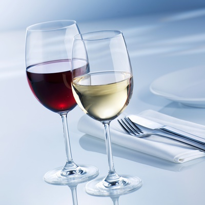 Glass of White Wine and Glass of Red Wine Beside Place-Setting Photographic Print by Alexander Feig