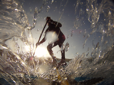 A Stand Up Paddleboarder Surfs a Wave Near Nags Head Pier Stampa fotografica di Brown, Skip