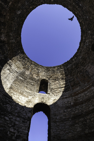 A Solitary Bird Flies Above an Opening in a Dome in Diocletian's Palace in Split Fotografisk tryk af Jonathan Irish
