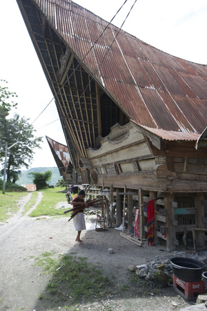 Batak Woman Carrying Skeins of Yarn to the Looms under Her Traditional Batak House Photographic Print by Annie Owen
