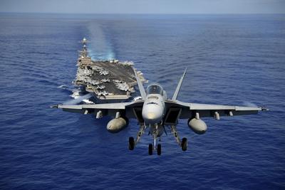 An F-A-18E Super Hornet Flying Above USS John C. Stennis Photographic Print