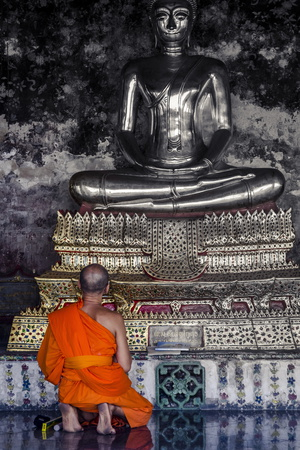 A Monk Prays in Front of a Golden Buddha, Wat Suthat, Bangkok, Thailand, Southeast Asia, Asia Photographic Print by Andrew Taylor