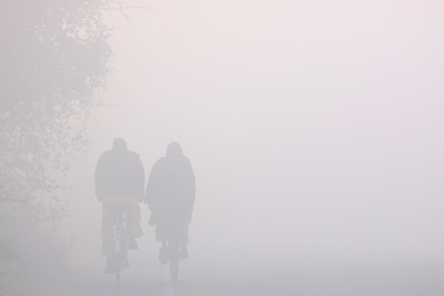 Cyclists Make their Way Through Thick Fog Photographic Print by Raminder Pal Singh