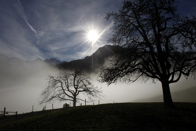 The Sun's Rays Filter Through Thin Clouds Above a Misty Scene Photographic Print by Urs Flueeler