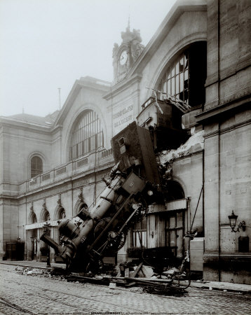 The picture is a very famous one, in black and white. There is an old steam train that is falling from the windows of the first floor old building.