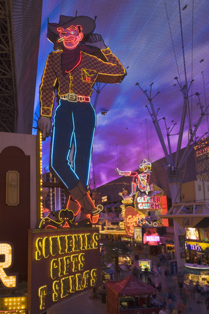 The Famous Ivegas Vici Neon Cowboy Stands among Other Signs on Fremont Street in the Iglitter Gulch Photographic Print by David Davis
