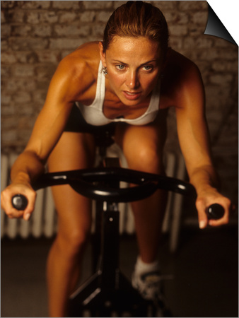 Young Woman Exercising on a Stationary Bike Poster