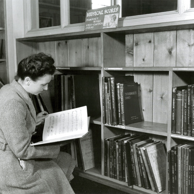 Reading a Score in a Music Library Photographic Print