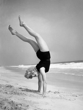 Woman Does Handstand on the Beach (B&W) Photographic Print by Hulton Archive
