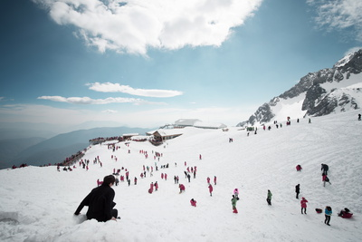 Mostly Local Tourists Playing in the Snow on Top of Jade Dragon Snow Mountain Near Lijiang Photographic Print by Andreas Brandl