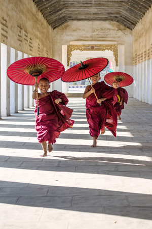Myanmar, Mandalay Division, Bagan. Three Novice Monks Running with Red Umbrellas in a Walkway (Mr) Fotografisk tryk af Matteo Colombo