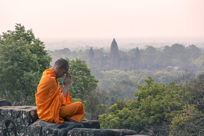 Cambodia, Siem Reap, Angkor Wat Complex. Monk Meditating with Angor Wat Temple in the Background Photographic Print by Matteo Colombo