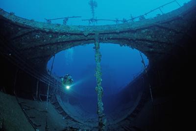 Scuba Diver Exploring a Shipwreck, Papua New Guinea, Coral Sea. Photographic Print by Reinhard Dirscherl