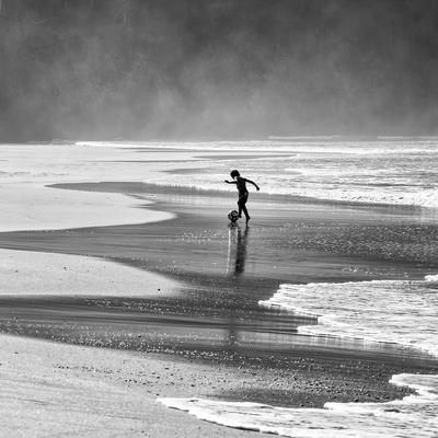 A Young Boy Kicks a Ball on Itamambuca Beach in Ubatuba, Brazil Photographic Print by Alex Saberi