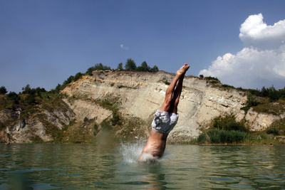 A Man Jumps into a Lake, Formerly an Abandoned Mine, in the Village of Moscanica Photographic Print by Dado Ruvic