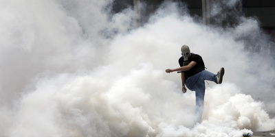 A Demonstrator Kicks Back a Smoke Grenade Canister During a Protest in Athens' Syntagma Square Photographic Print by John Kolesidis