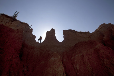 A Hiker Pauses on a Mountain in the El Cuzco Region of the Tatacoa Desert in Southwest Colombia Photographic Print by Jose Gomez