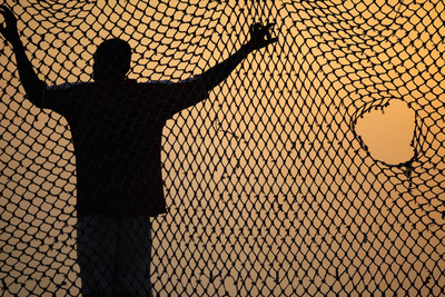 A Goalkeeper Rests on the Net as Angolan Youths Play Soccer on the Beach in the Capital Luanda Photographic Print by Mike Hutchings