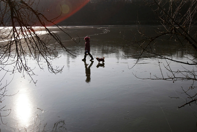 A Girl Walks Her Dog on a Frozen Pond During a Cold Winter Day in Prague Photographic Print by David W Cerny