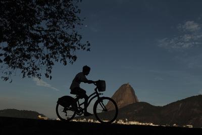 A Boy Rides His Bicycle Along the Guanabara Bay in Rio De Janeiro Lámina fotográfica por Pilar Olivares
