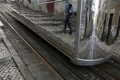 A Passer-By Is Reflected in the Mirrors of a Bica Funicular Tram in Lisbon Photographic Print by Nacho Doce