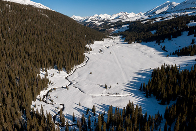 A River Snakes Through Snow Covered Ground in the Mountains in Carbondale, Colorado Photographic Print by Pete McBride