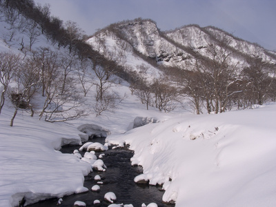 Winter Landscape with a Stream and Mountains in Hokkaido, Japan