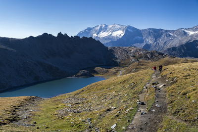 Hikers Walking on the Colle Del Nivolet Beside Rossett Lake (Lago Rossett) Photographic Print by Roberto Moiola
