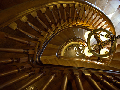 Looking Down a Spiral Staircase Past a Hanging Chandelier Kunst på metal af Amy & Al White & Petteway