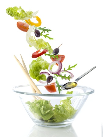 Salad Ingredients Falling into a Glass Bowl Photographic Print by Caroline Martin