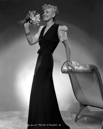 Penny Singleton standing and Holding Flowers in Black Elegant Dress Photo by  Movie Star News
