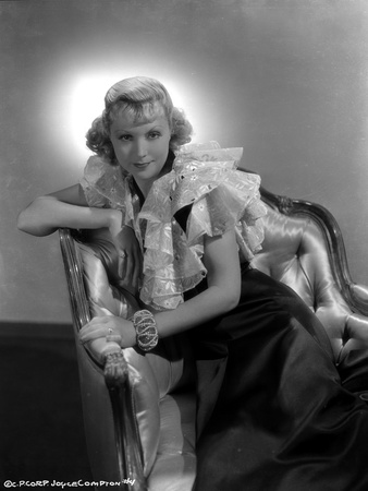 Joyce Compton sitting on a Chair and wearing a Black and White Dress in a Classic Portrait Photo by  Movie Star News
