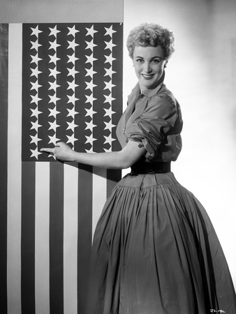 Jan Sterling Posed Facing the Right in Velvet Dress with Rolled Up Sleeves and Pleated Skirt while  Photo by  Movie Star News