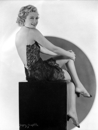 Joyce Compton sitting on a Chair wearing a Backless Dress in a Classic Portrait Photo by  Movie Star News