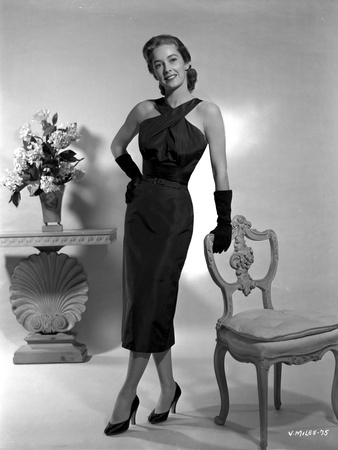 Vera Miles posed standing in a black, ankle length, halter dress and gloves, while leaning onto a c Photo by  Movie Star News