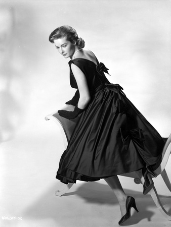 Vera Miles kneeling onto a chaise lounger, looking behind her shoulder, wearing a black, sleeveless Photo by  Movie Star News