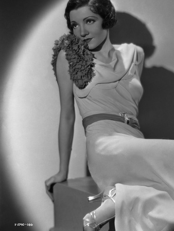 Claudette Colbert sitting in White Dress with Heels Photo by  Movie Star News