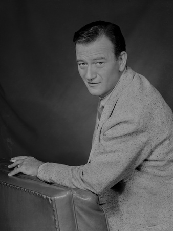 John Wayne Leaning on a Foam, wearing a Suit Photo by  Movie Star News