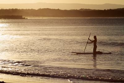 A Woman on a Stand-Up Paddleboard Heads Towards Main Beach, Noosa, at Sunset Photographic Print by William Gray