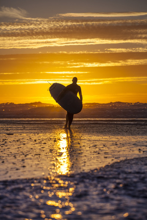Uk, Cornwall, Polzeath. a Woman Comes in from an Evening Surf Against a Stunning Sunset. Fotografie-Druck von Niels Van Gijn