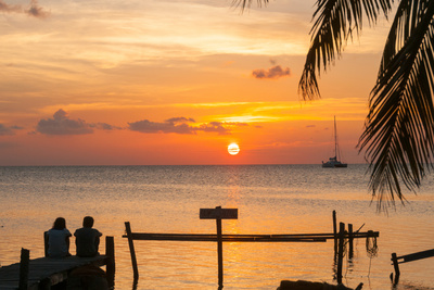 A Couple Watches the Sunset at Caye Caulker Village Photographic Print by Jordi Busque