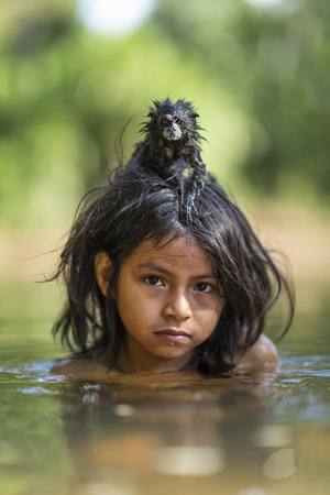 A Pet Saddleback Tamarin Hangs on Tight to a Matsigenka Girl as She Swims in the Yomibato River Photographic Print by Charlie Hamilton James