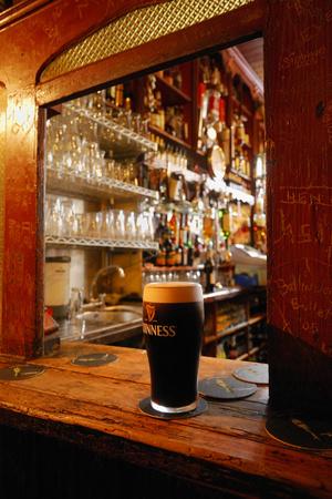 A Pint of Dark Beer Sits in a Pub Service Window Sträckt kanvastryck av Jim Richardson