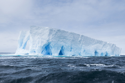 A Natural Arch Formation Inside a Tabular Iceberg Photographic Print by Jeff Mauritzen