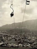 Man Riding Chair Lift Above Town Photographic Print by Jerry Cooke