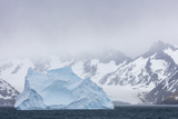 South Georgia Island. Large Iceberg Floats Past Mountains Photographic Print by Jaynes Gallery